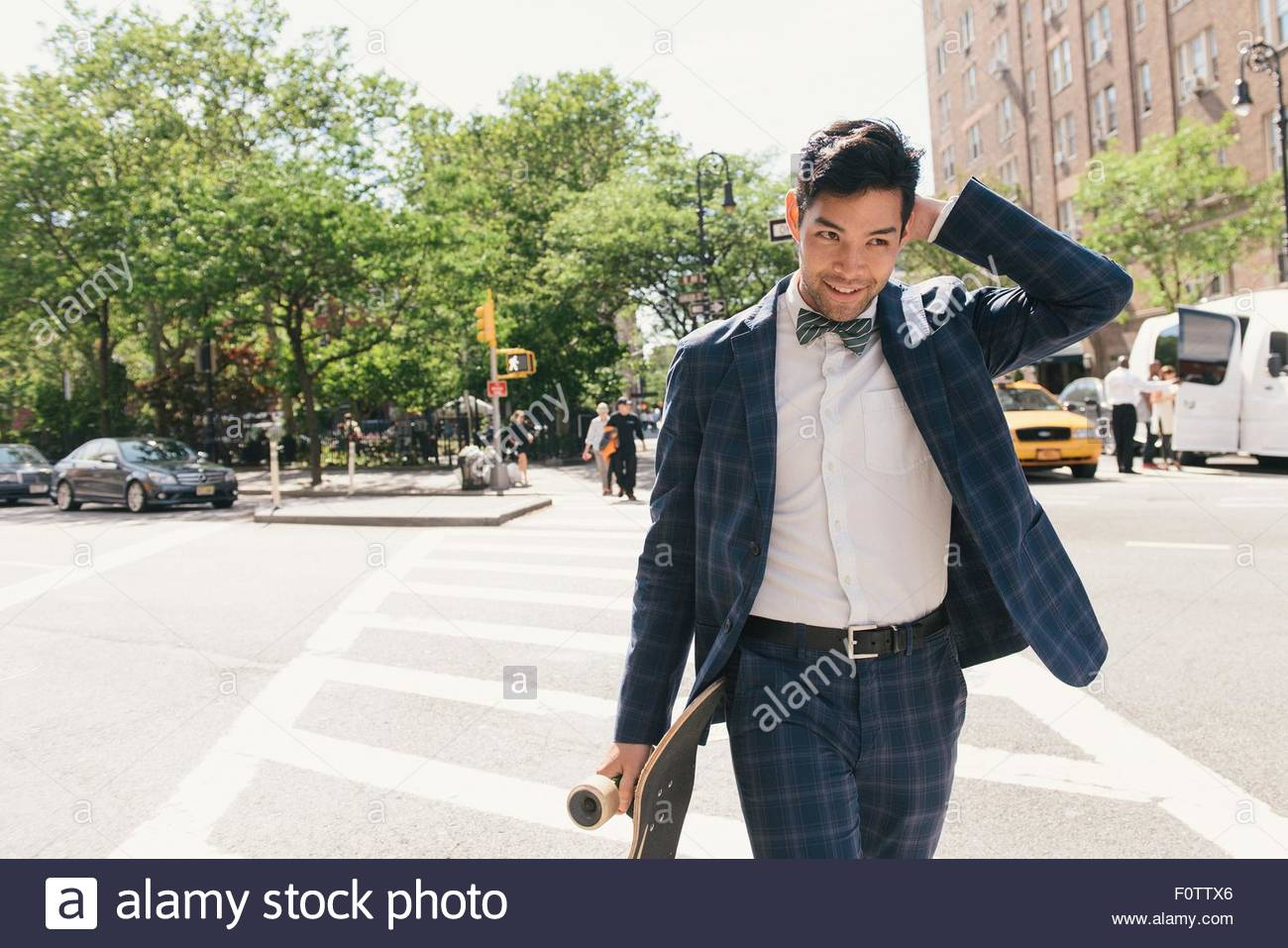 Suit wearing male skateboarder crossing road, West Village, Manhattan, USA - Stock Image