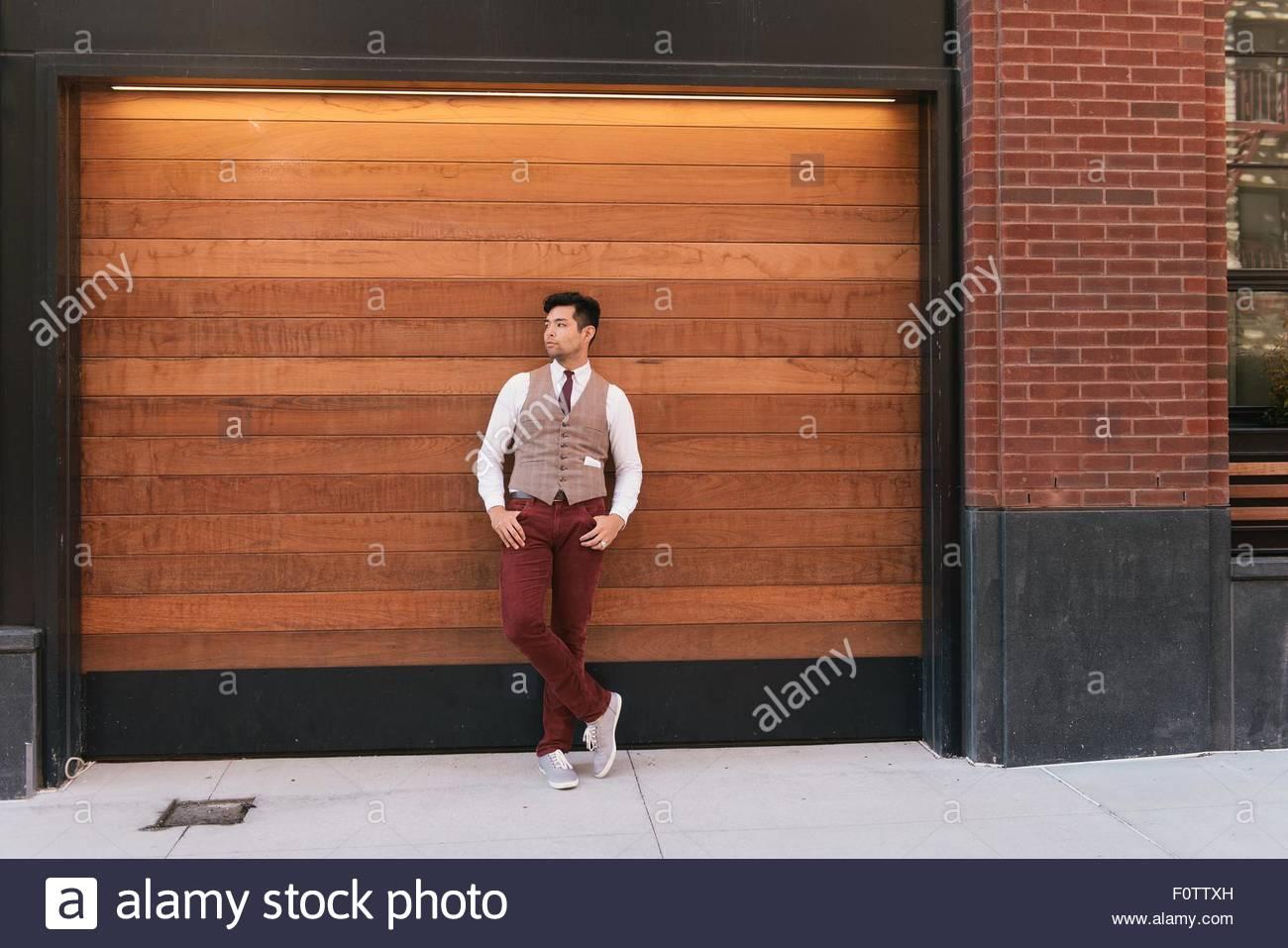 Stylish mid adult man leaning against shutter, West Village, Manhattan, USA - Stock Image