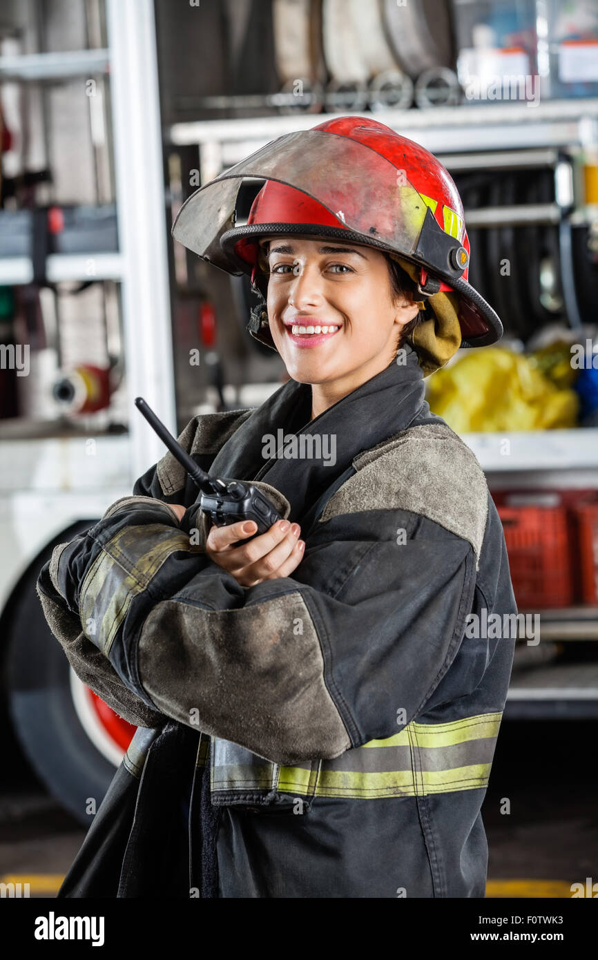 Happy Firewoman Holding Walkie Talkie Against Firetruck - Stock Image