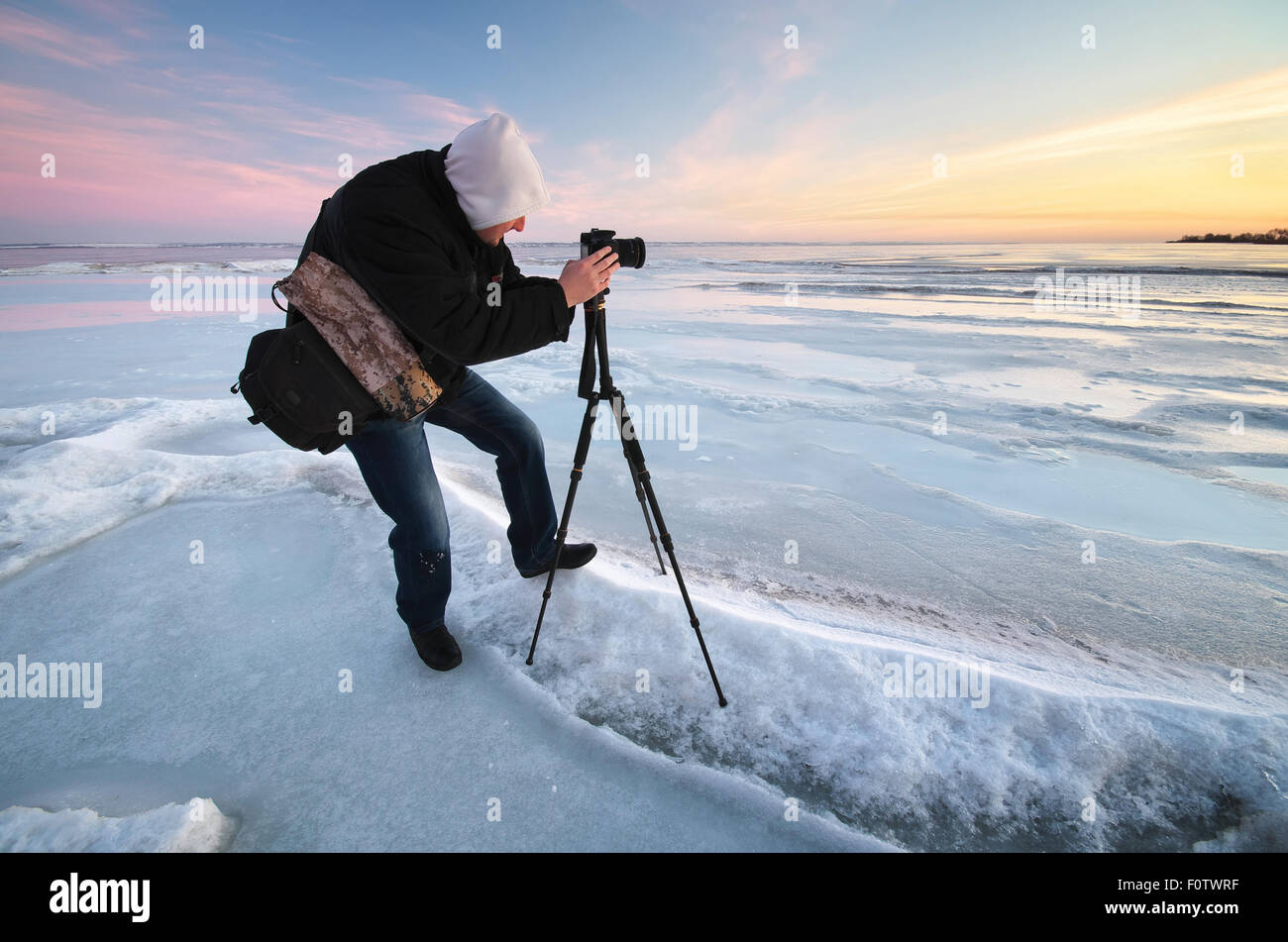 Photographer take pictures on the river bank in winter - Stock Image