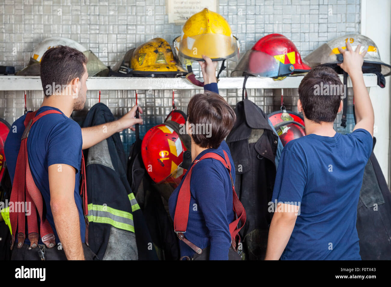 Firefighters Removing Helmets From Shelf - Stock Image