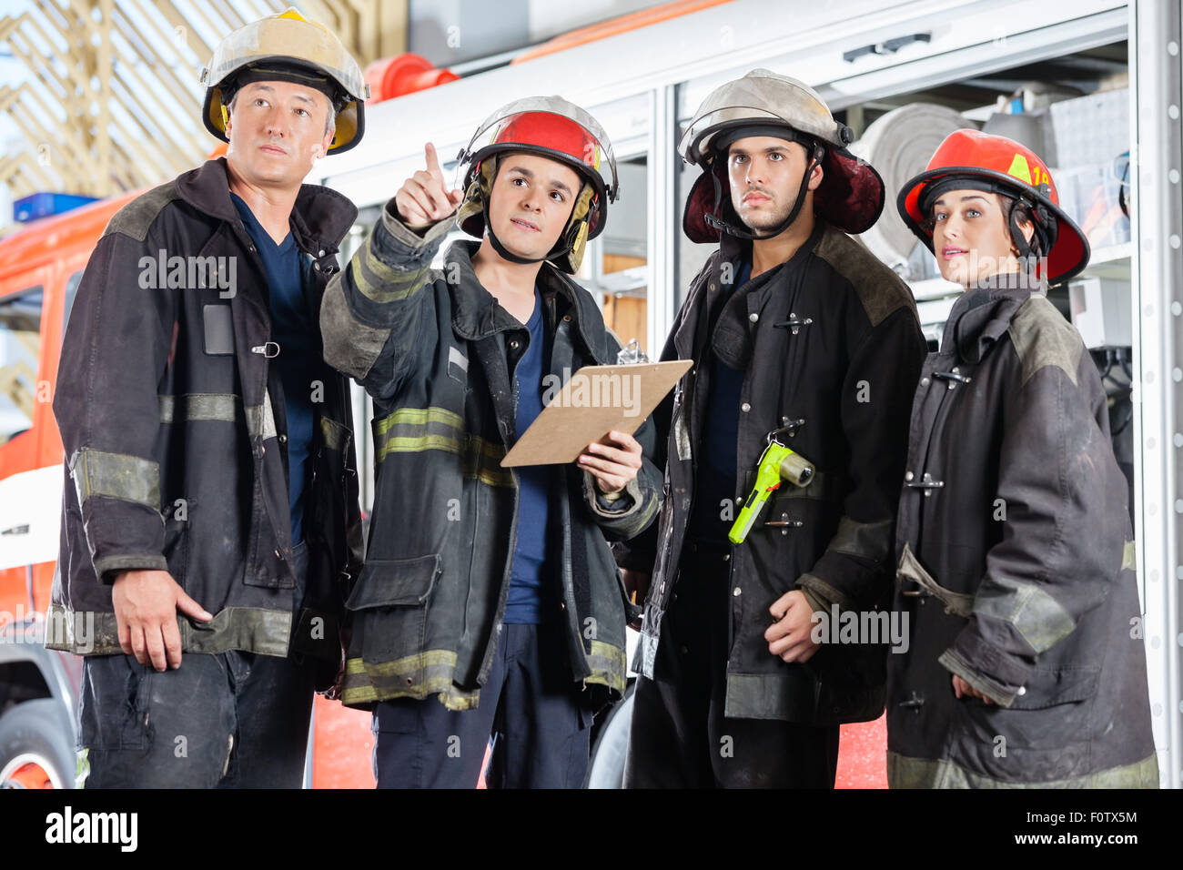 Firefighter Showing Something To Colleagues - Stock Image