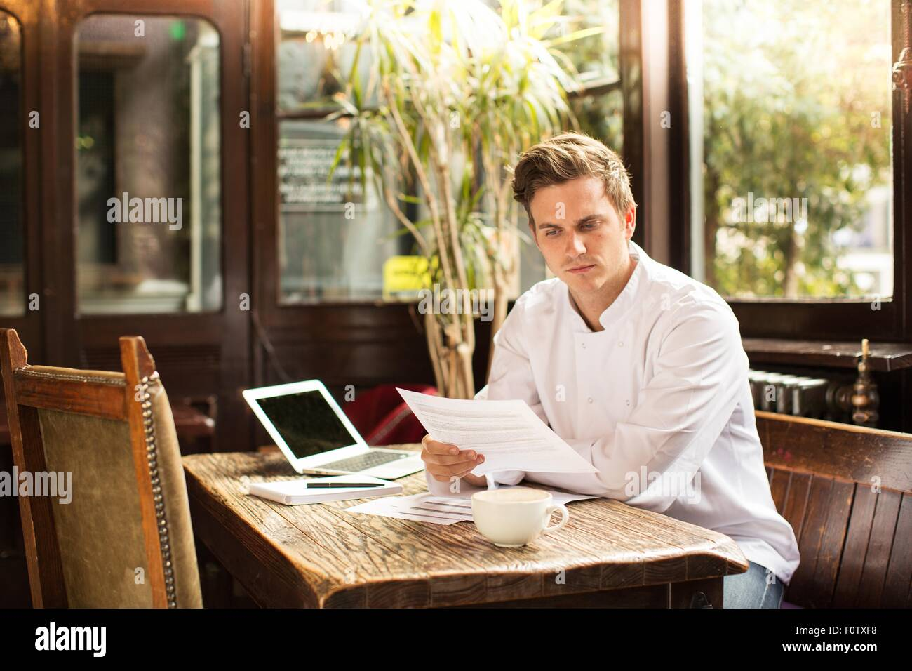 Young chef sitting at work looking at paperwork Stock Photo