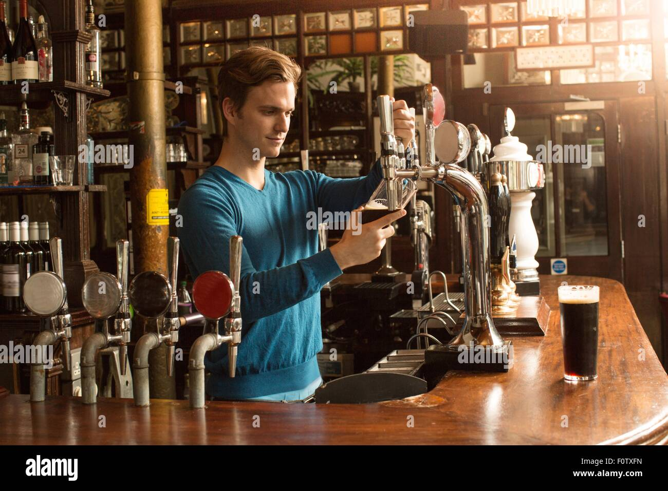 Young man working in public house, serving drinks - Stock Image