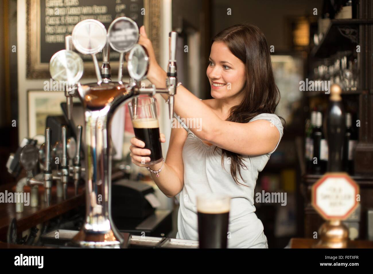 Mid adult woman working in public house, serving drinks - Stock Image