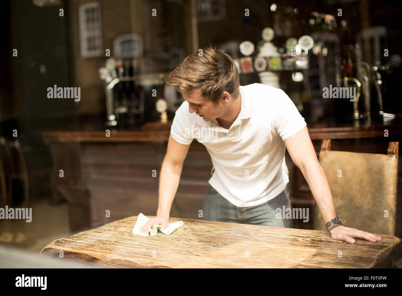 Young man cleaning table in public house - Stock Image