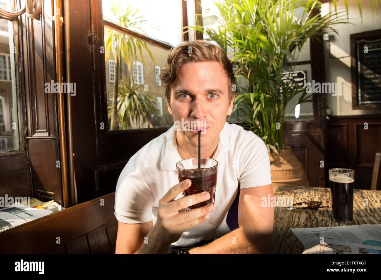 Portrait of young man drinking through straw, looking at camera - Stock Image