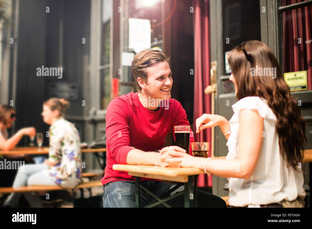 Couple sitting face to face in beer garden holding hands Stock Photo