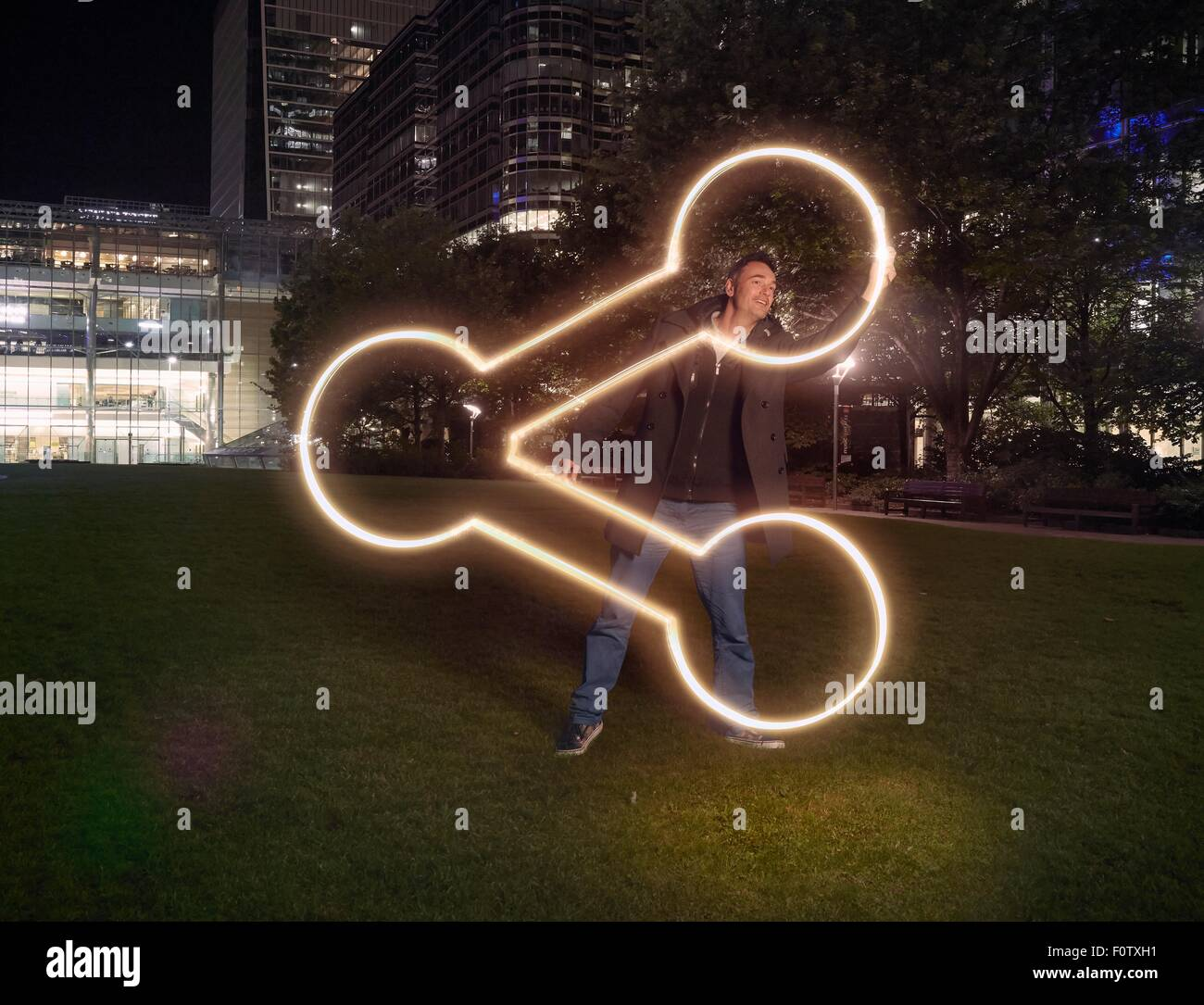 Artist painting share symbol outside office building at night - Stock Image