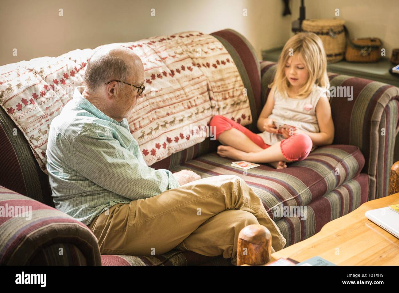 Grandfather and granddaughter playing cards on sofa - Stock Image