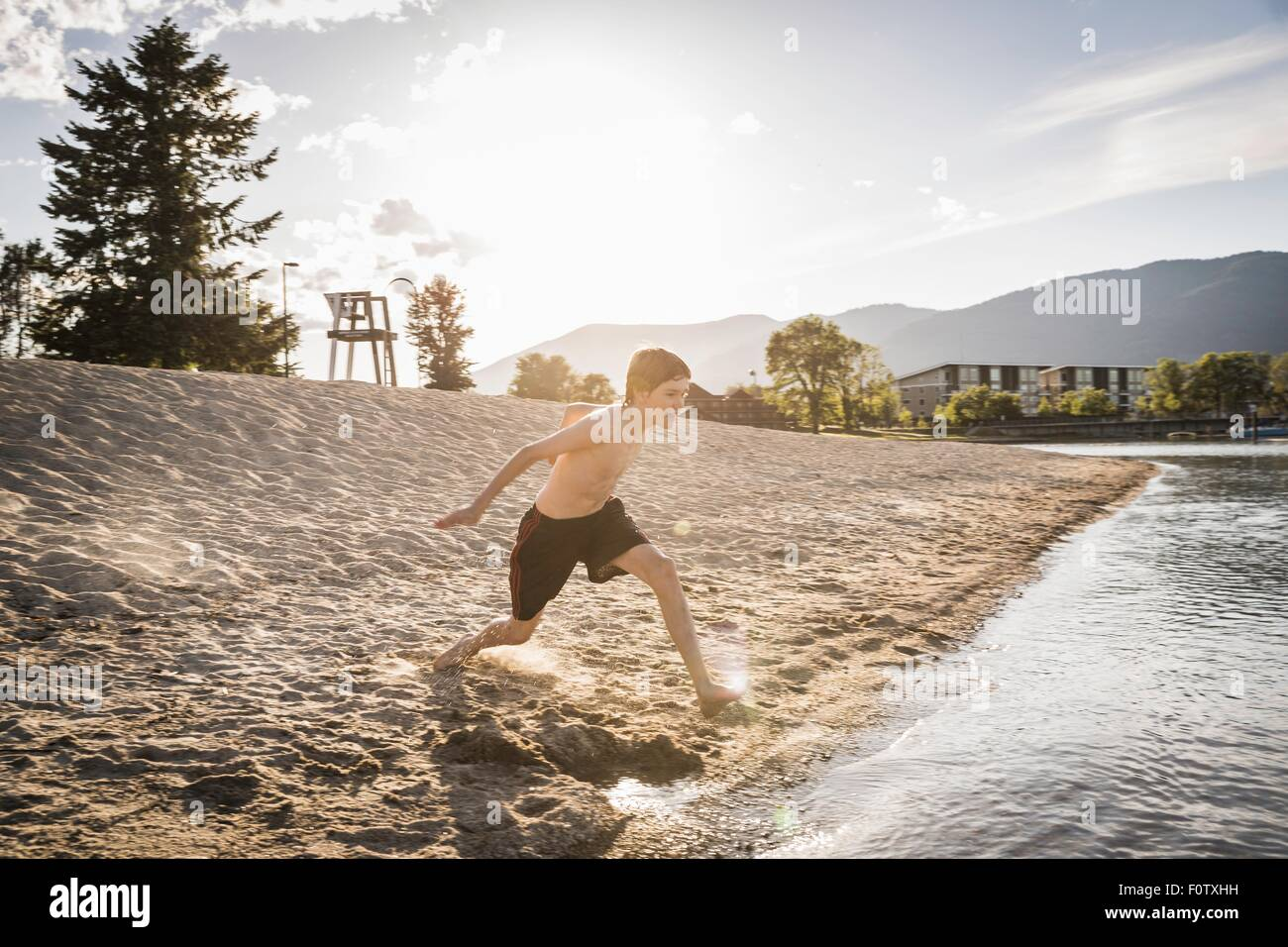 Teenage boy running to waters edge on beach, Sand Point, Idaho, USA - Stock Image