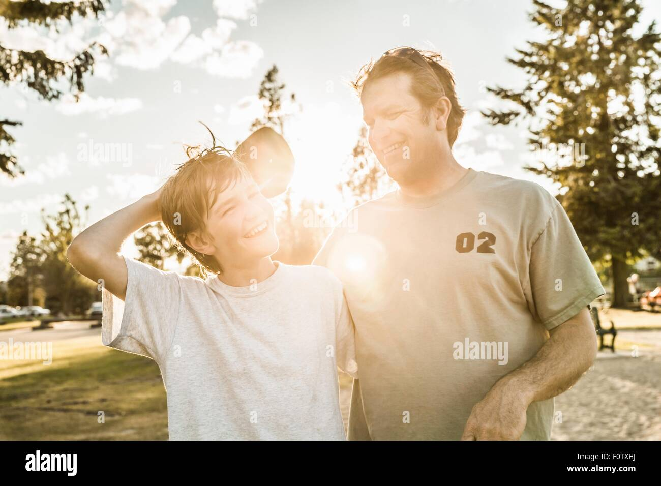 Father and son smiling in sunlight - Stock Image