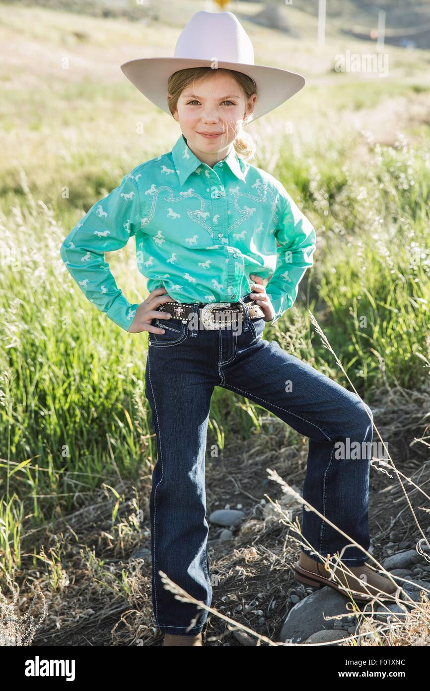 Girl wearing cowboy hat with hands on hips, portrait - Stock Image