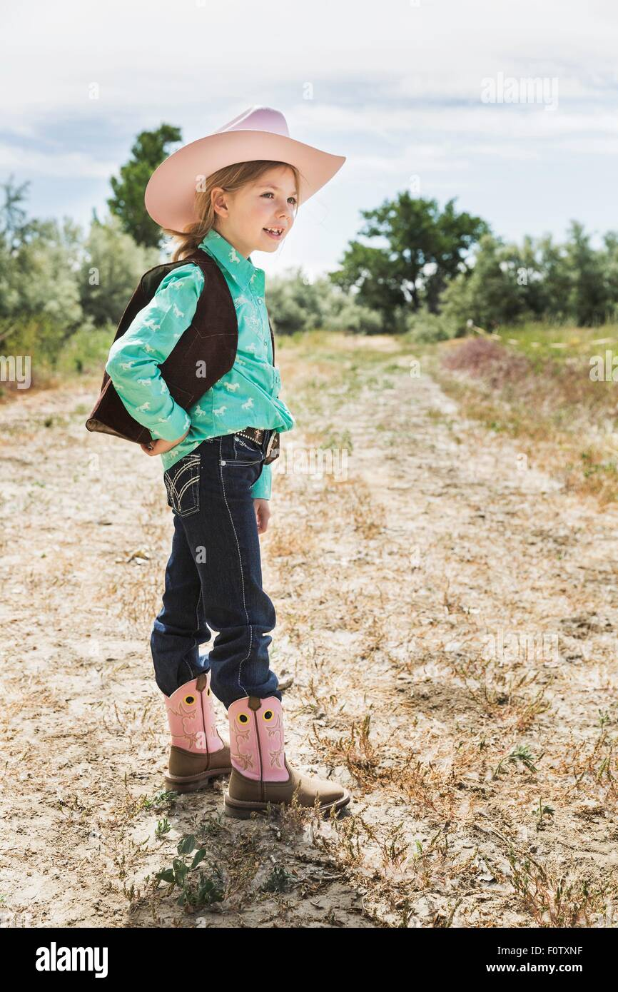 Girl wearing cowboy hat and boots on path - Stock Image