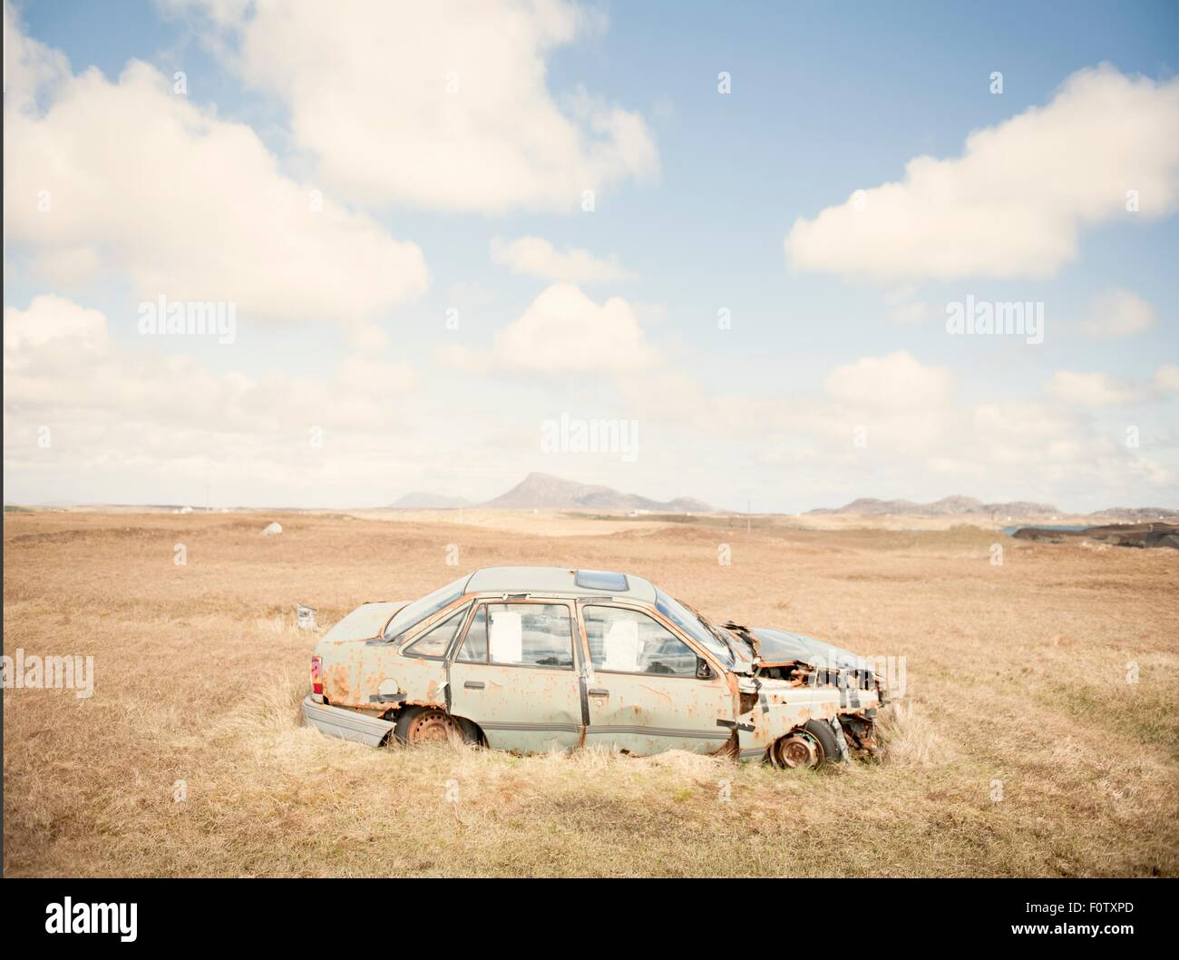 Landscape with rusty abandoned car, Isle of South Uist, Scotland, UK - Stock Image