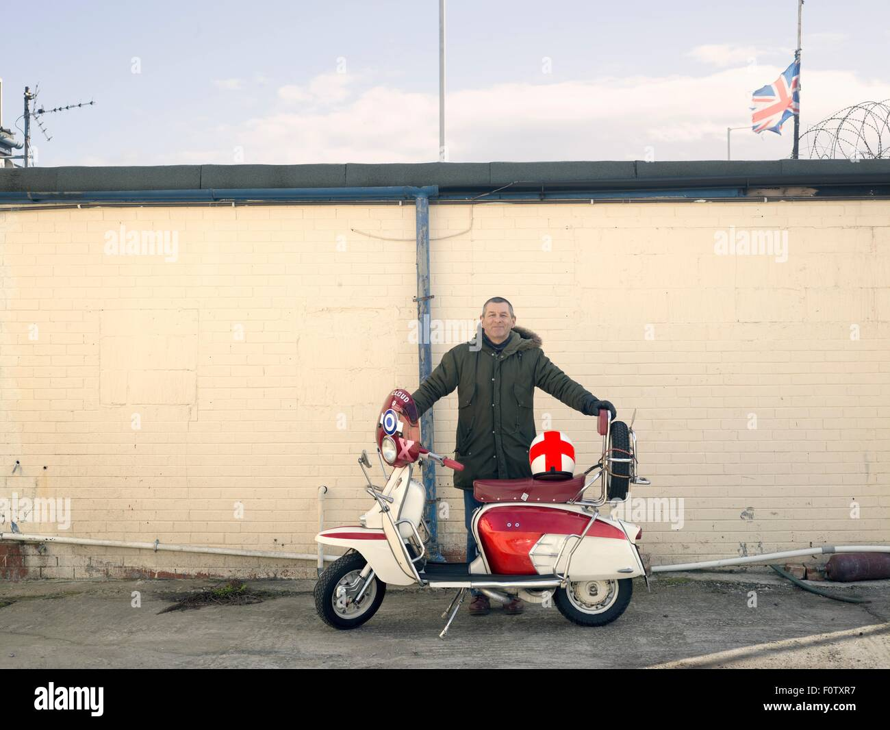 Portrait of mature male mod with moped in front of wall - Stock Image
