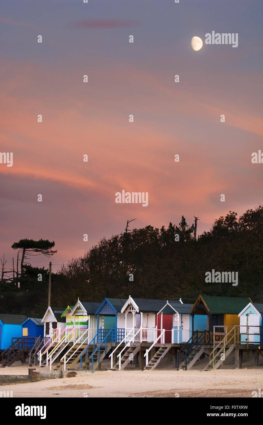 Row of multi-colored beach huts in moonlight, Norfolk England, UK - Stock Image
