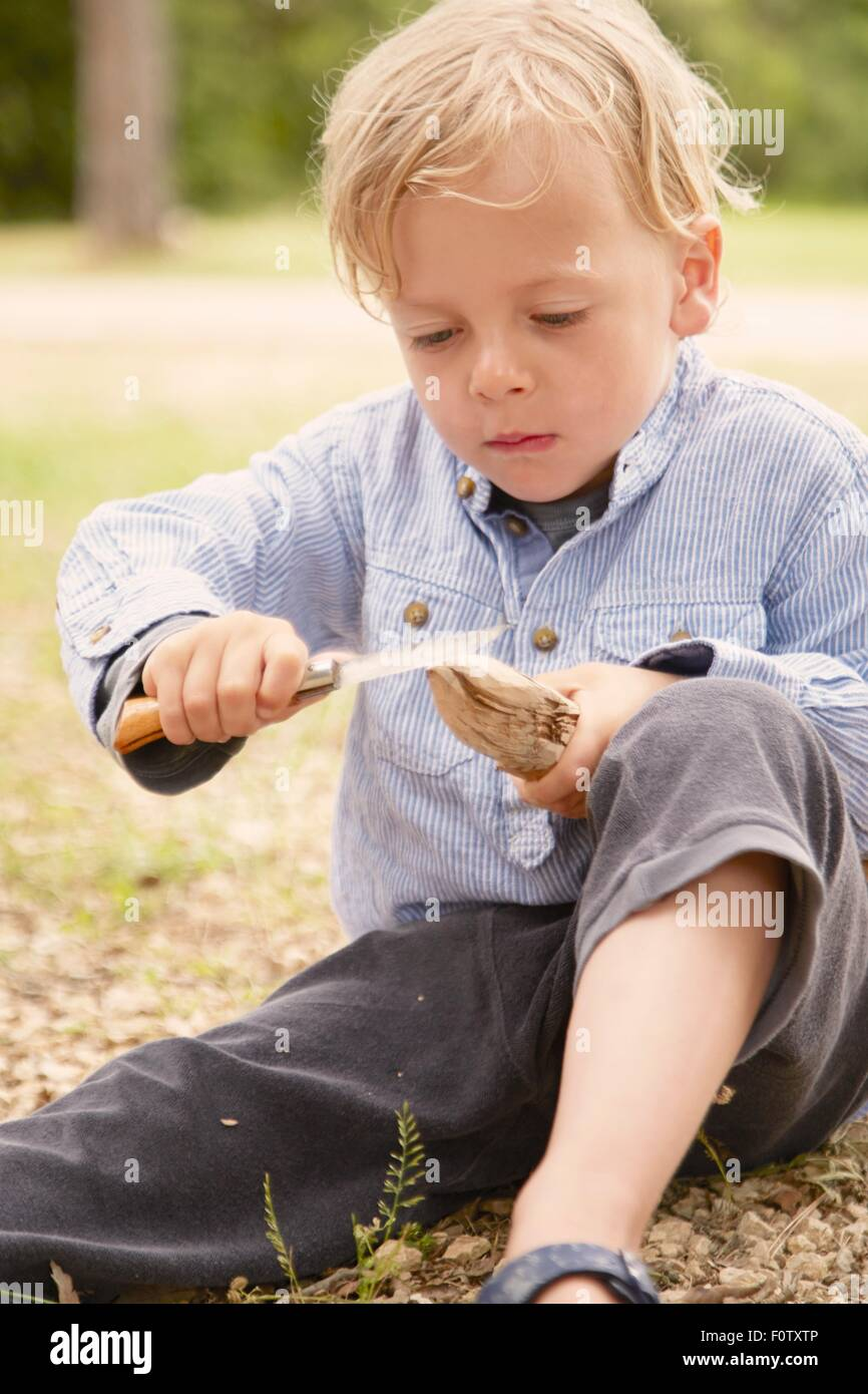 Boy carving stick with penknife, Lopar, Rab Island, Croatia - Stock Image