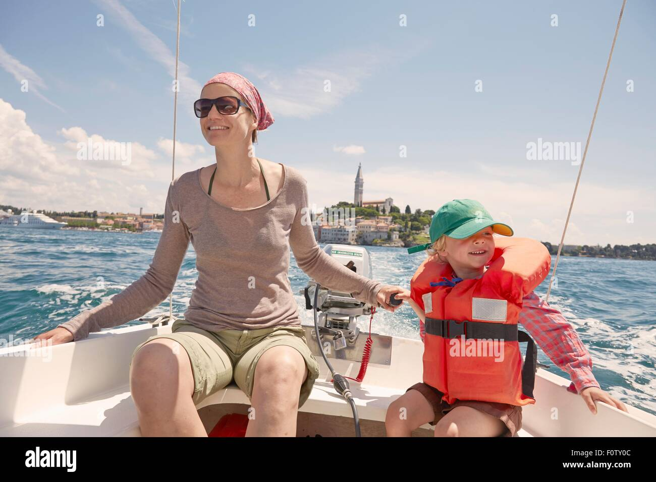 Mature woman with son steering motor boat, Rovinj, Istria Peninsula, Croatia - Stock Image