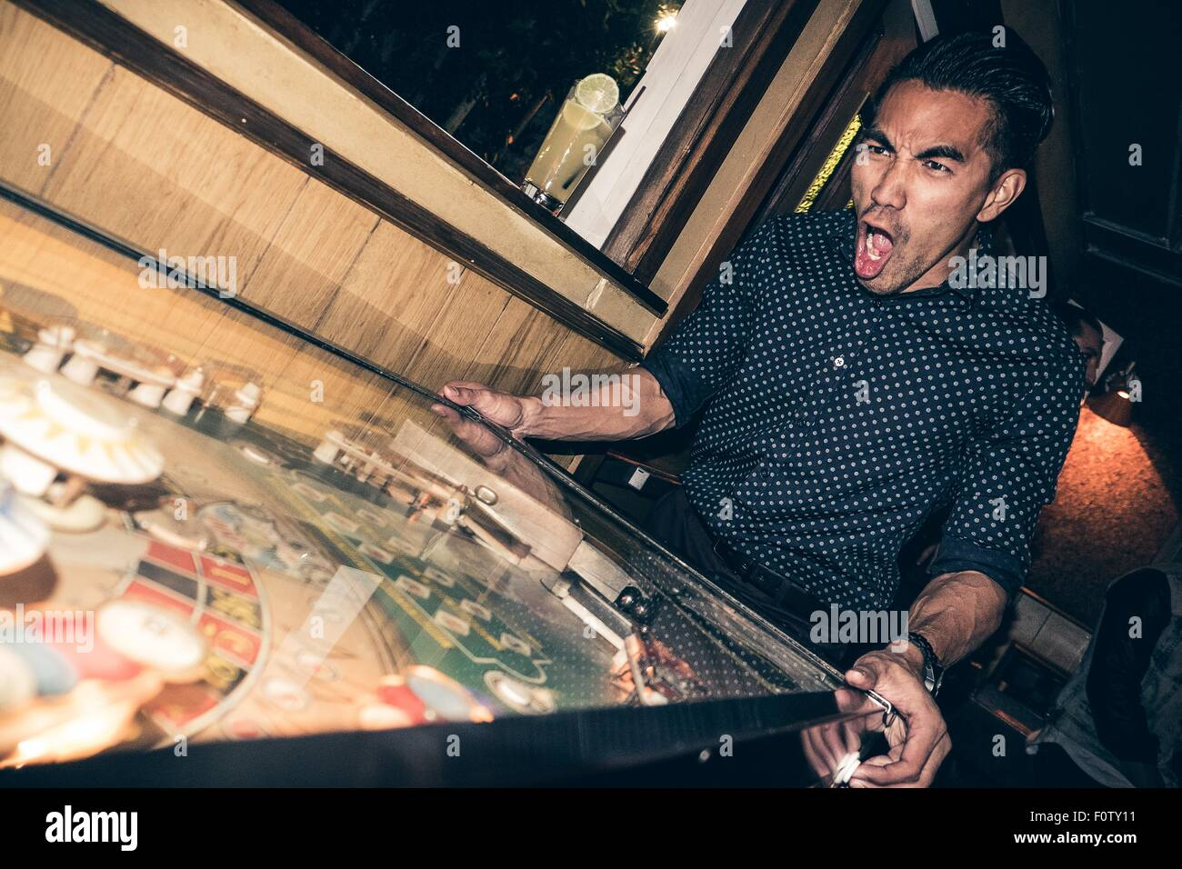 Young man playing pinball in bar, excited expression - Stock Image