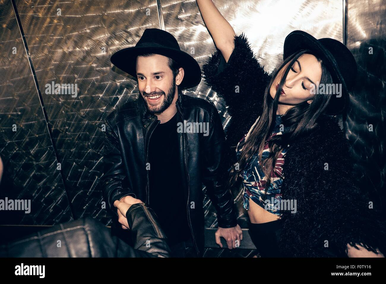 Young couple meeting friend in nightclub - Stock Image