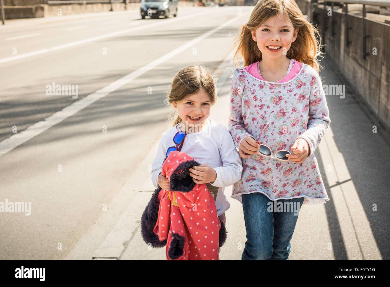 Two young girls walking down street together, smiling - Stock Image