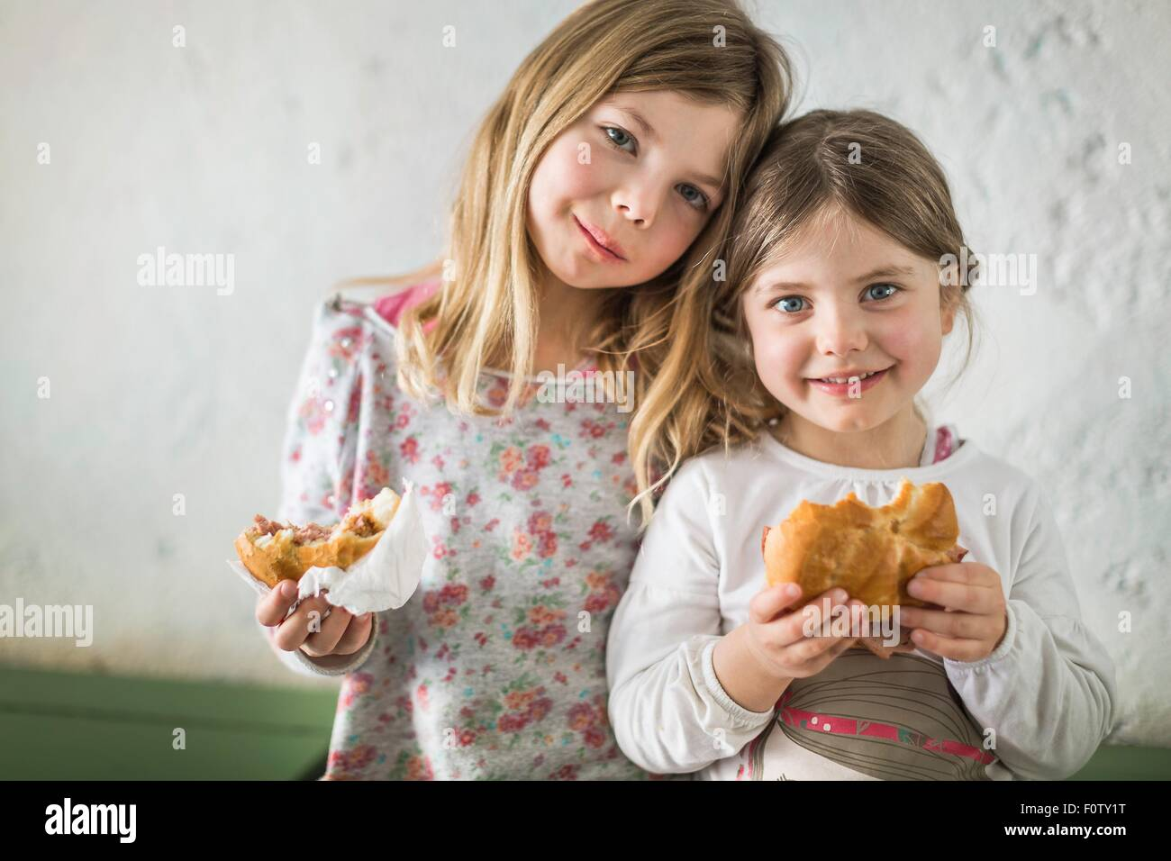 Two young girls eating savoury roll - Stock Image