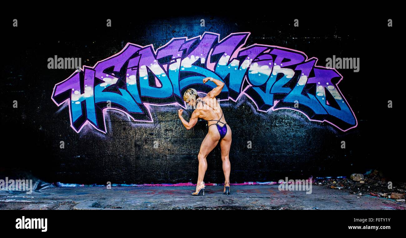 Female bodybuilder, flexing muscles, in pose, rear view - Stock Image