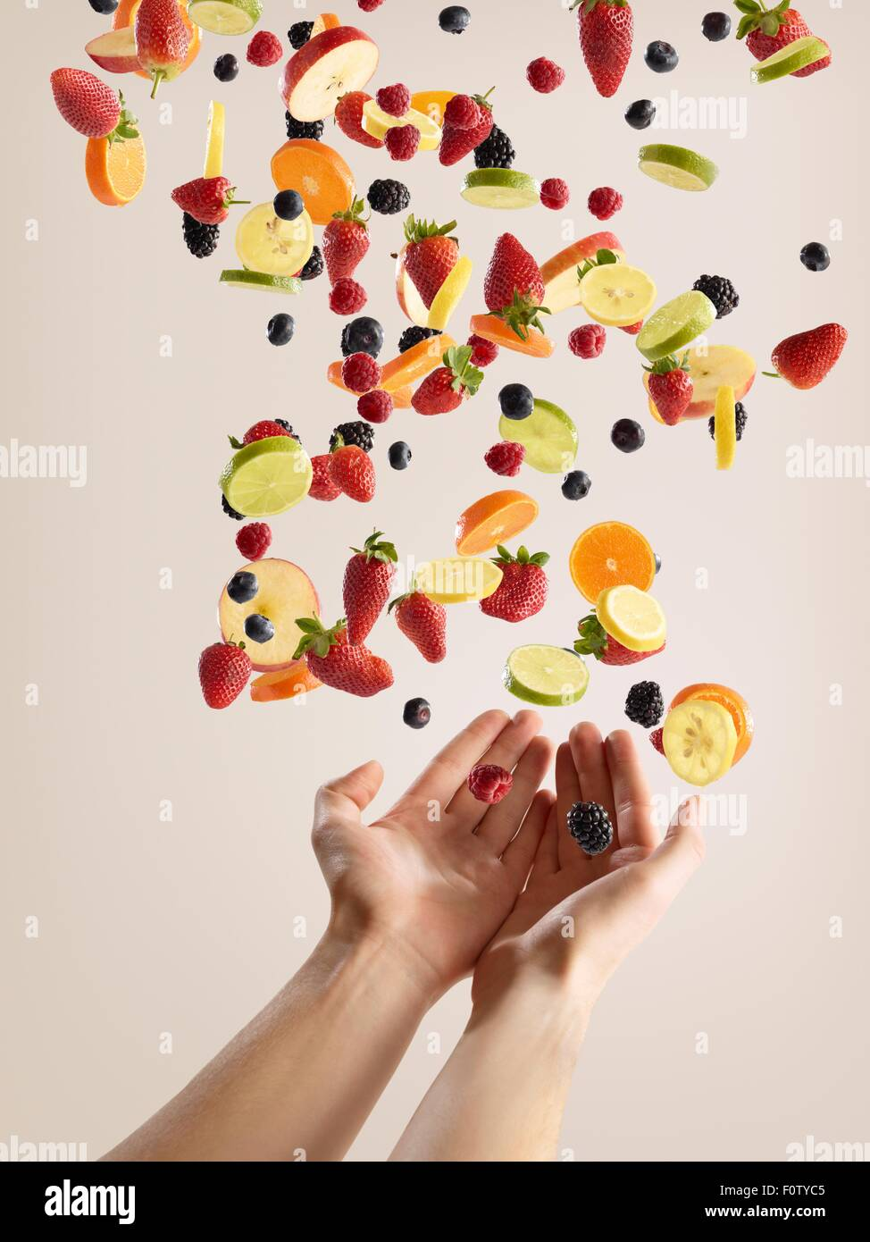 Teenage girls hands catching variety of fresh sliced fruit and berries - Stock Image