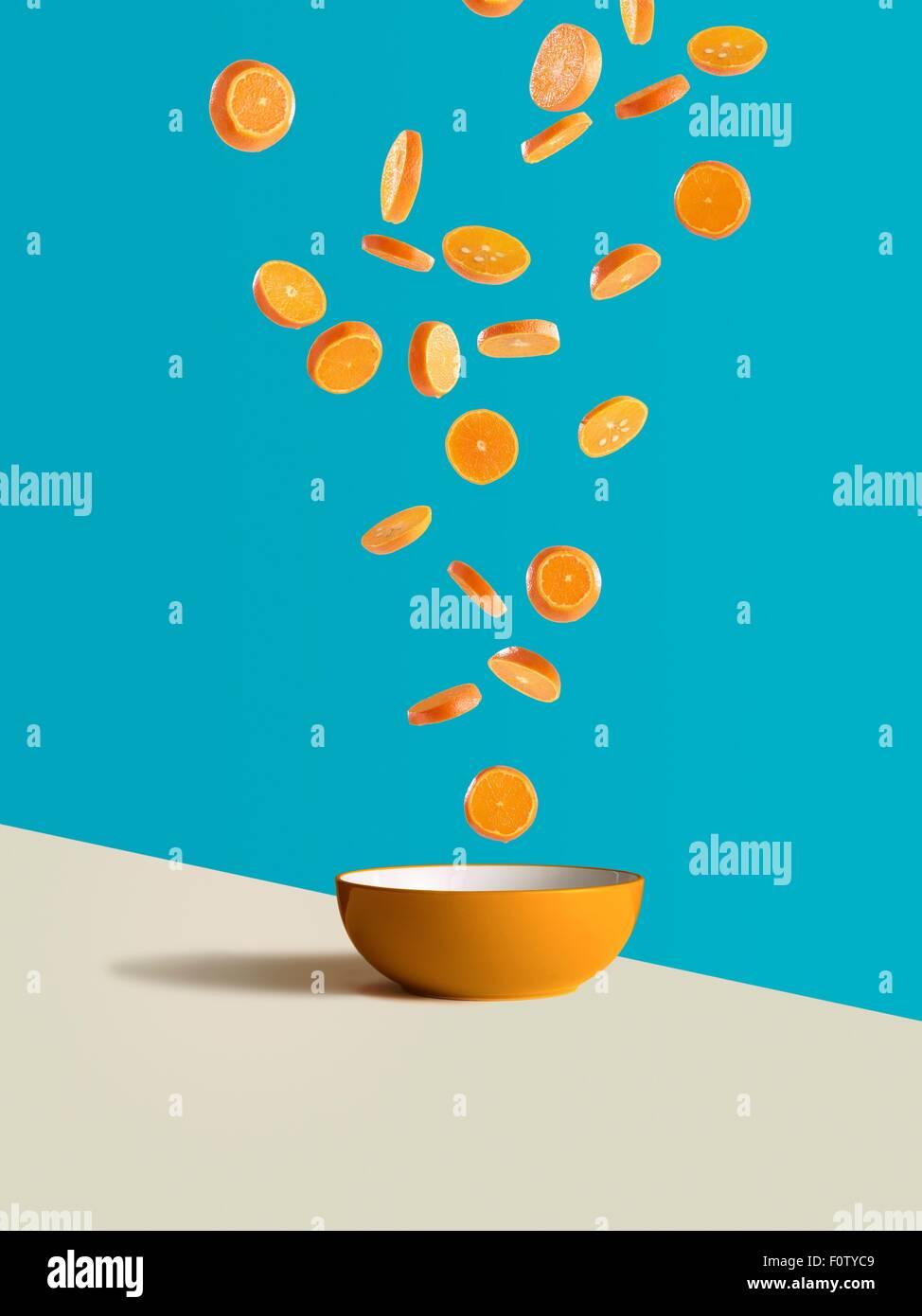 Fresh sliced oranges dropping into orange bowl - Stock Image