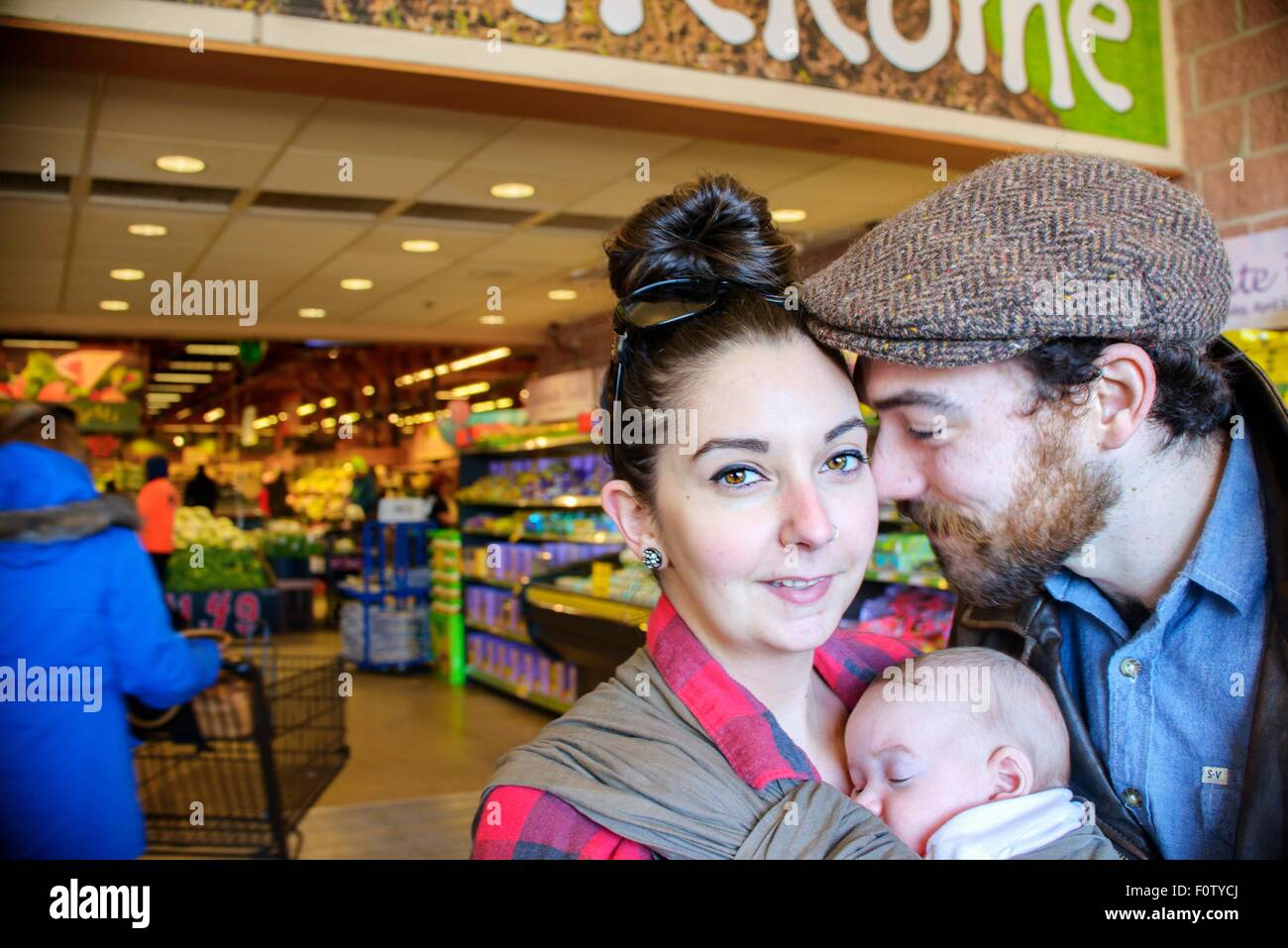 Mother and father with baby son in supermarket - Stock Image