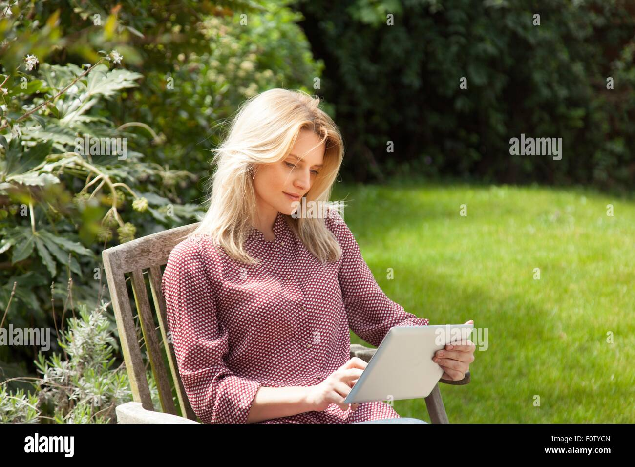 Mid adult woman in garden chair using touchscreen on digital tablet - Stock Image