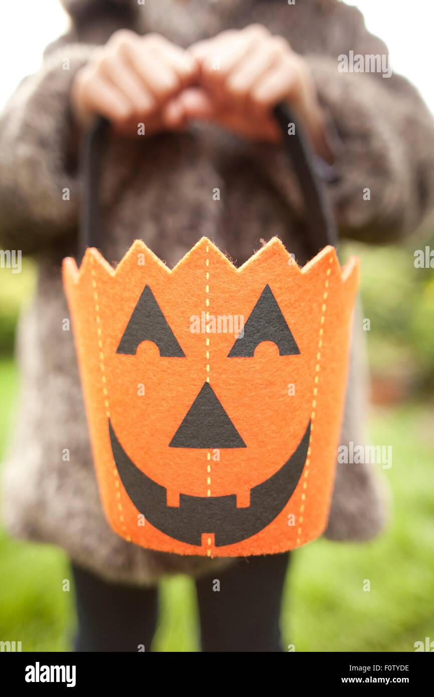 Girl holding up halloween pumpkin bag for trick or treating - Stock Image