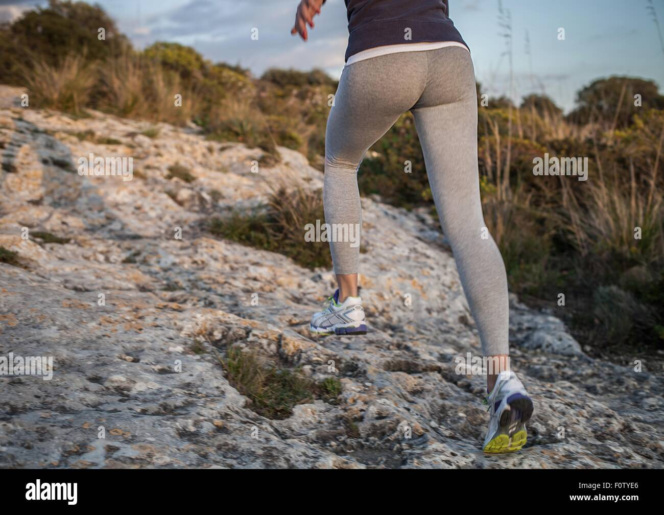 Young woman running uphill, rear view, low section - Stock Image
