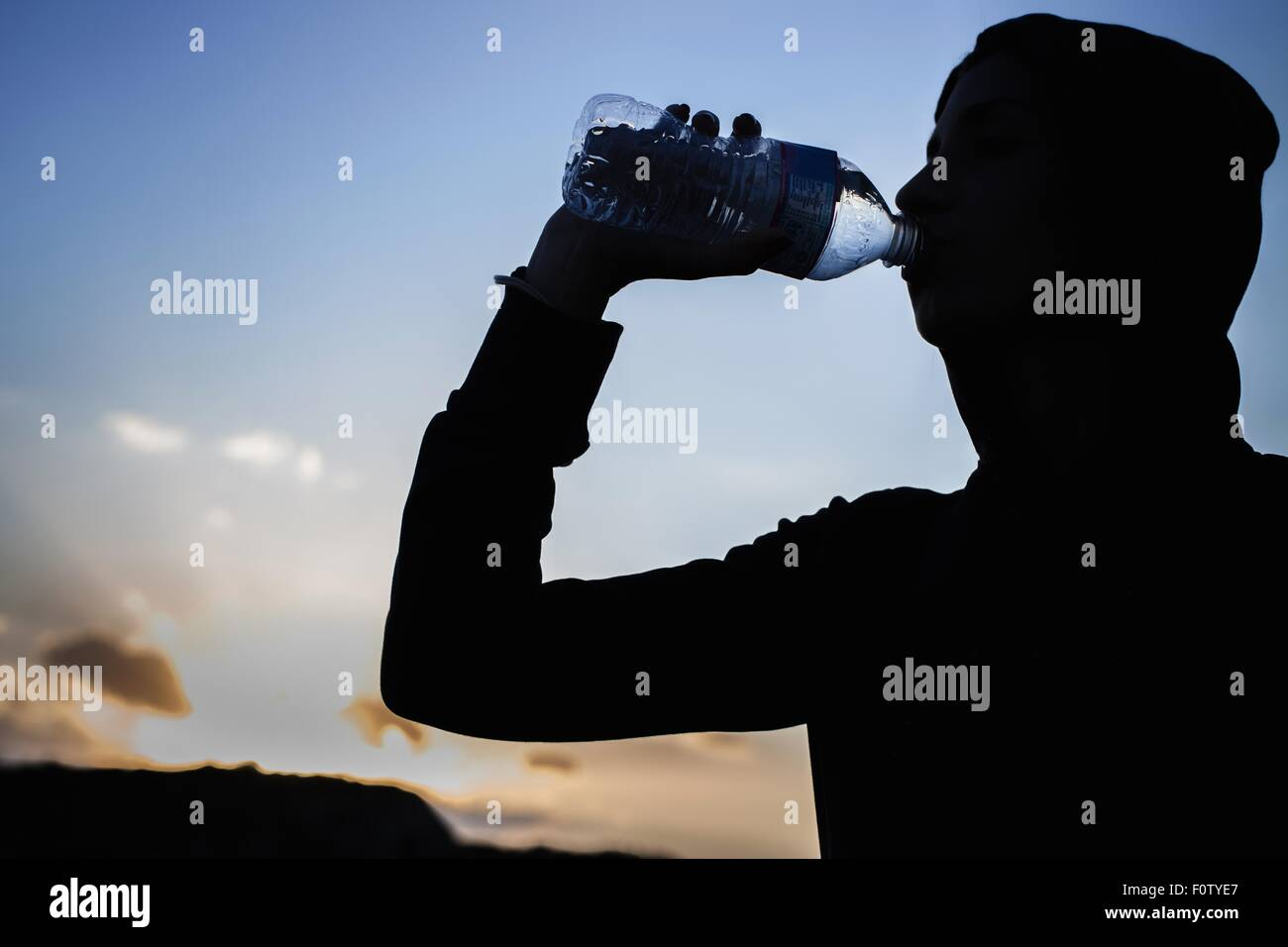 Young woman drinking from water bottle - Stock Image