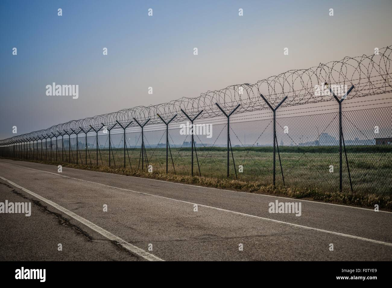 Barbed wire fence along empty road - Stock Image
