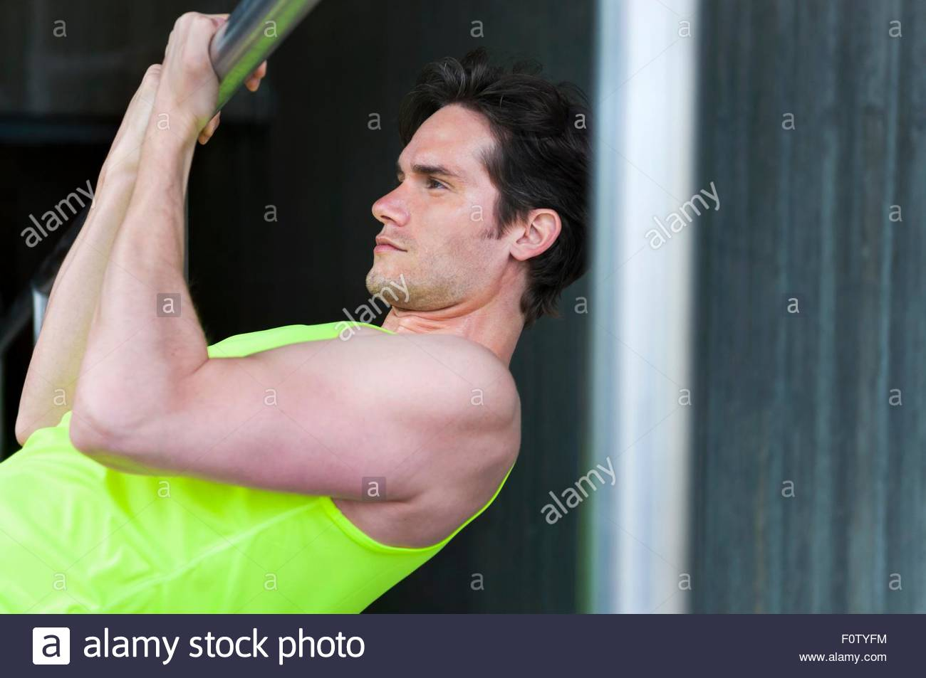 Portrait of mid adult man doing pull ups - Stock Image