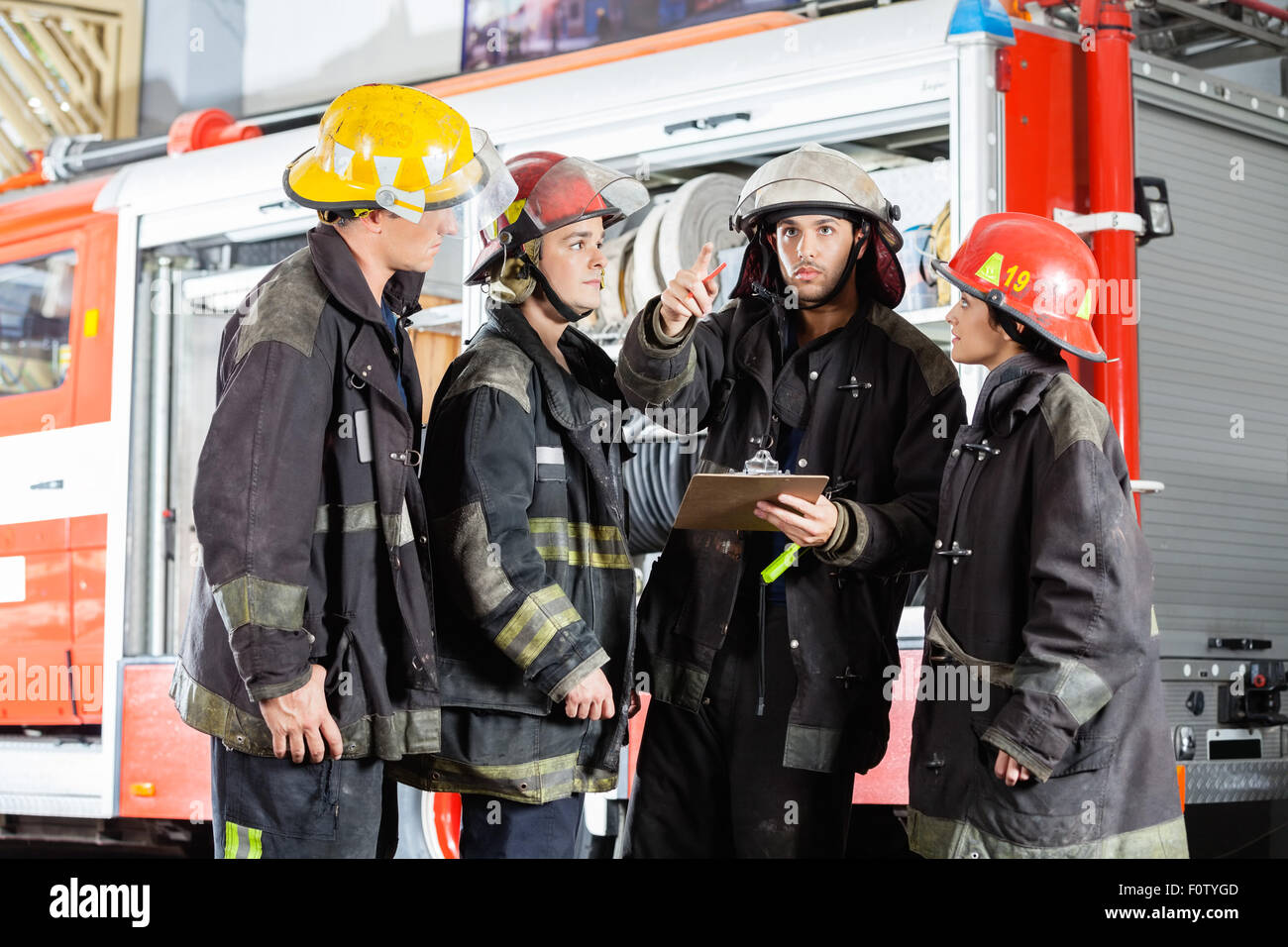 Firefighter Showing Something To Colleagues At Fire Station - Stock Image