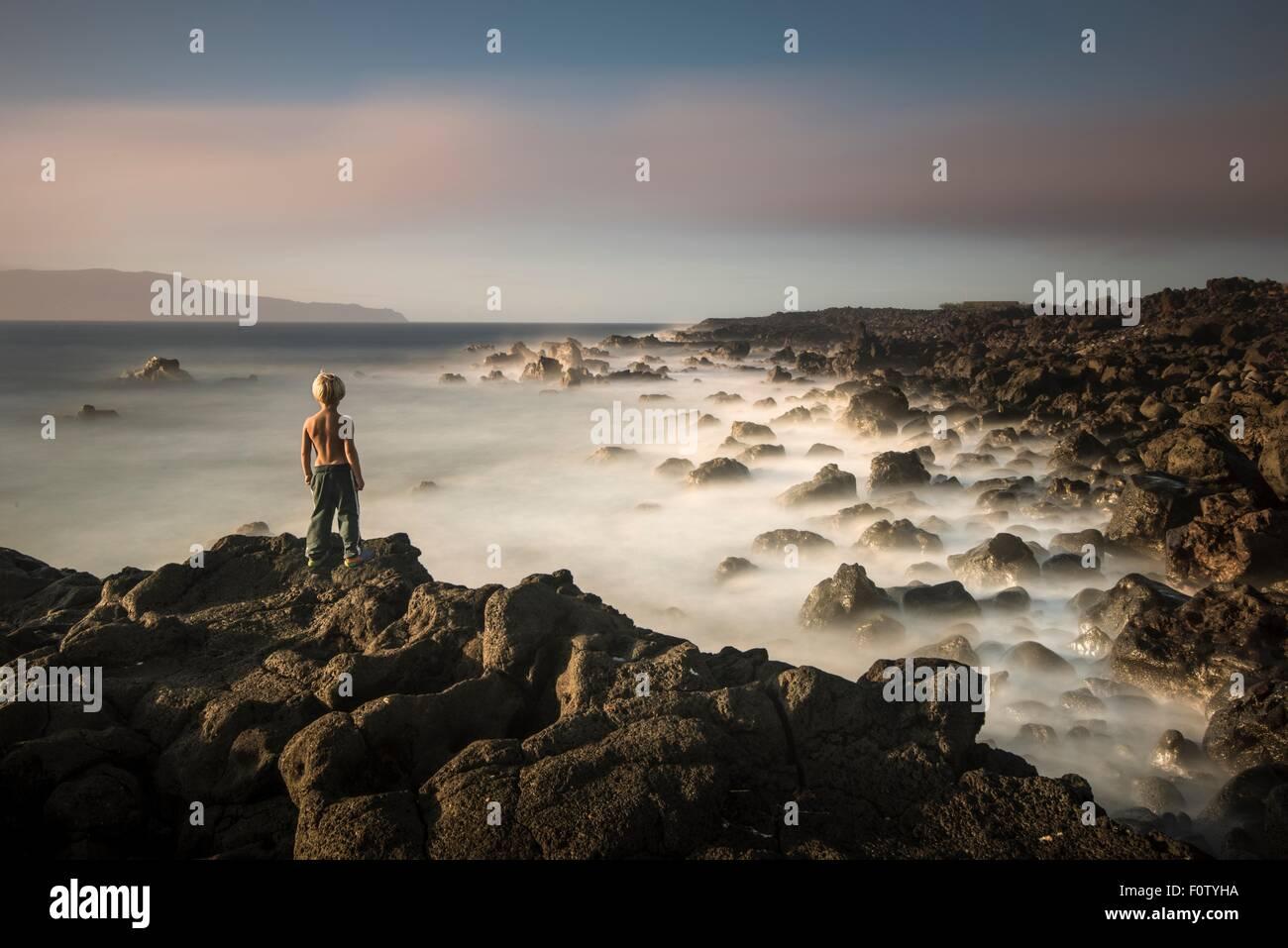 Boy on edge of cliff, Madalena, Pico, Azores, Portugal - Stock Image