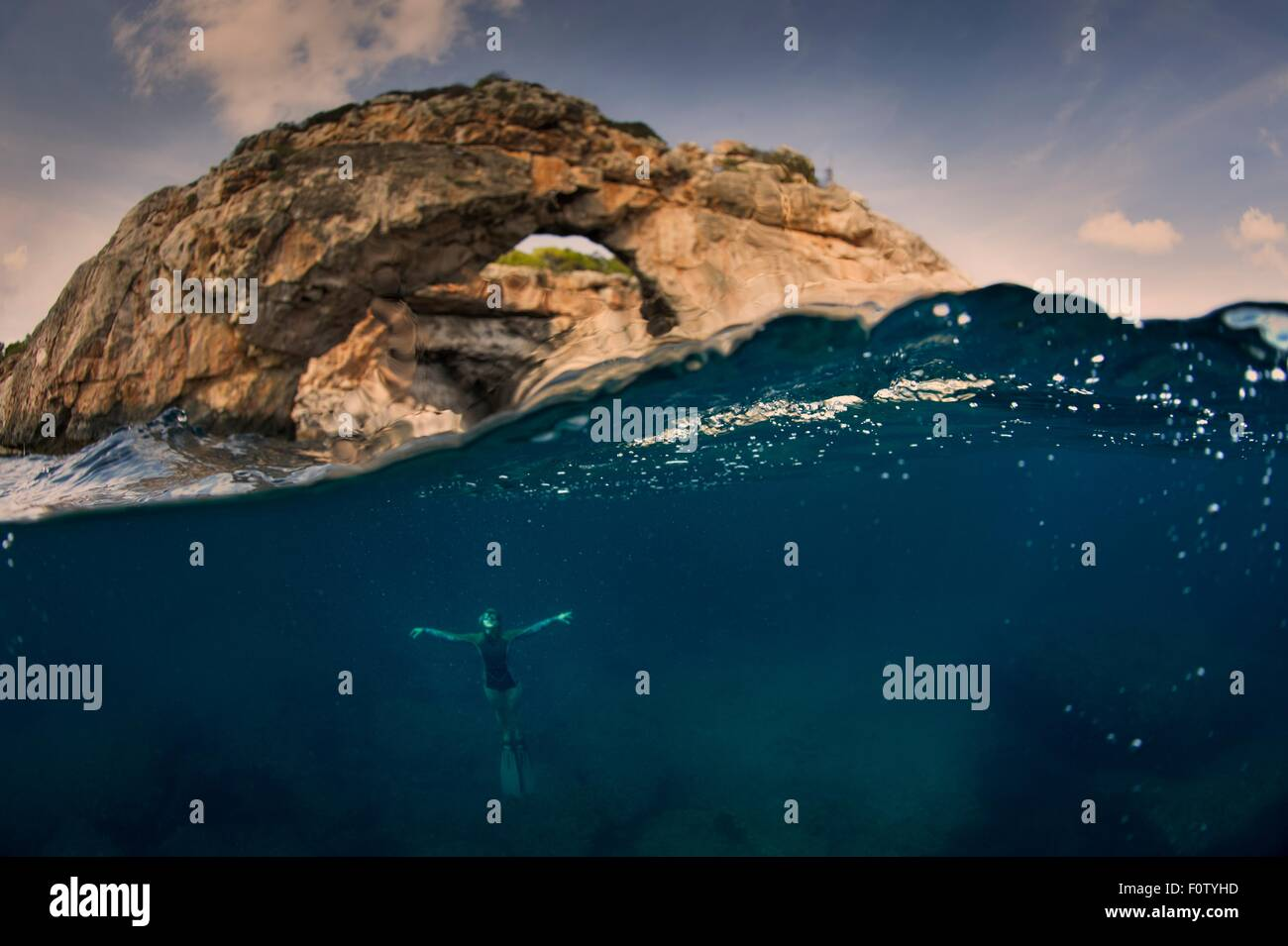 Woman underwater with arch, Santany, Mallorca, Spain - Stock Image