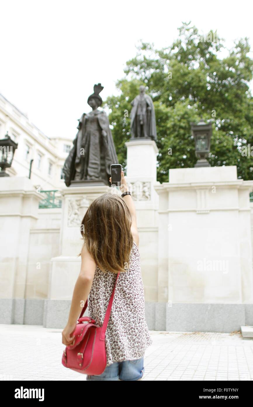 Young girl taking picture of Queen Mother statue with smartphone - Stock Image