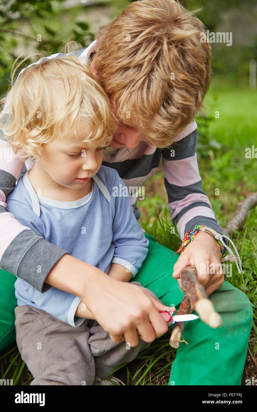 Boy sitting with younger brother using a penknife on twig in garden - Stock Image