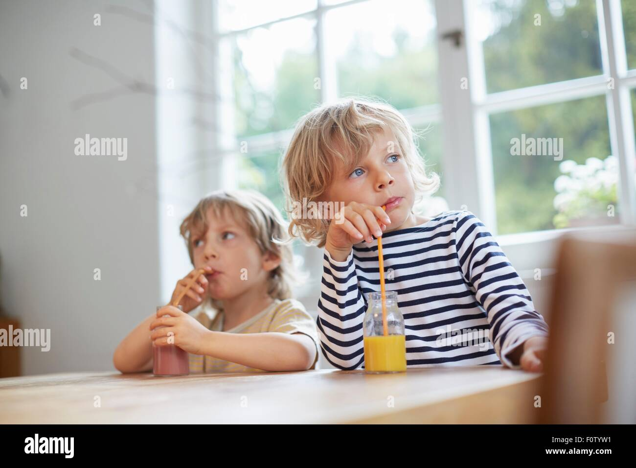 Two young brothers sitting at table drinking drinks with straws - Stock Image