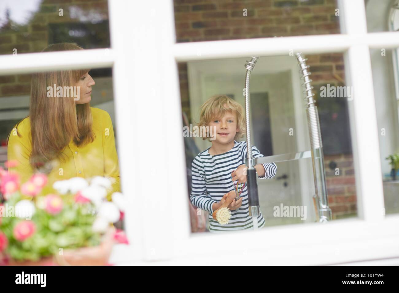 Mother and son doing washing up, view through window - Stock Image