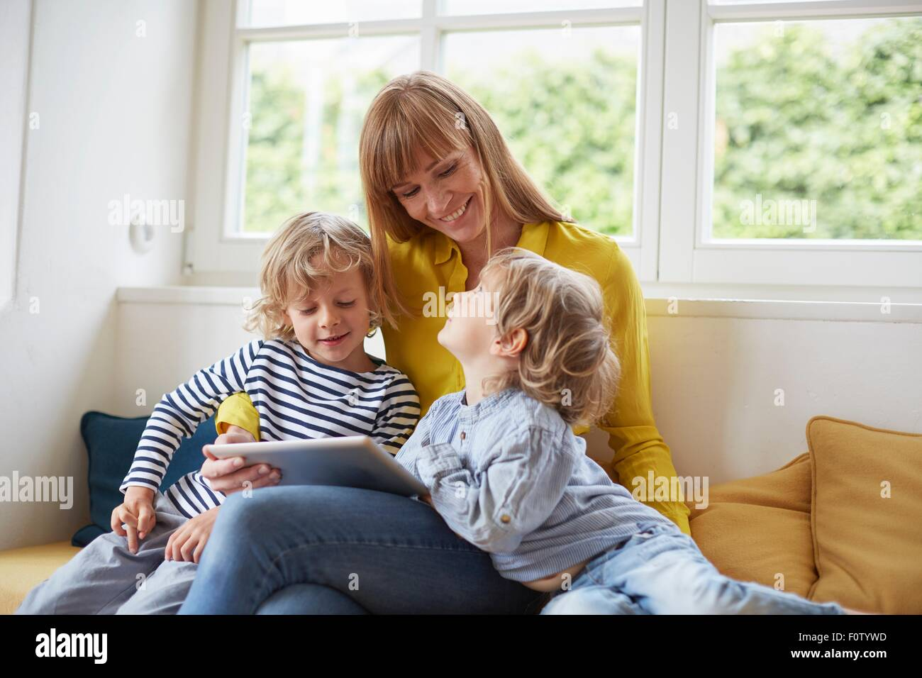 Mother and two sons, sitting in window seat, looking at digital tablet - Stock Image