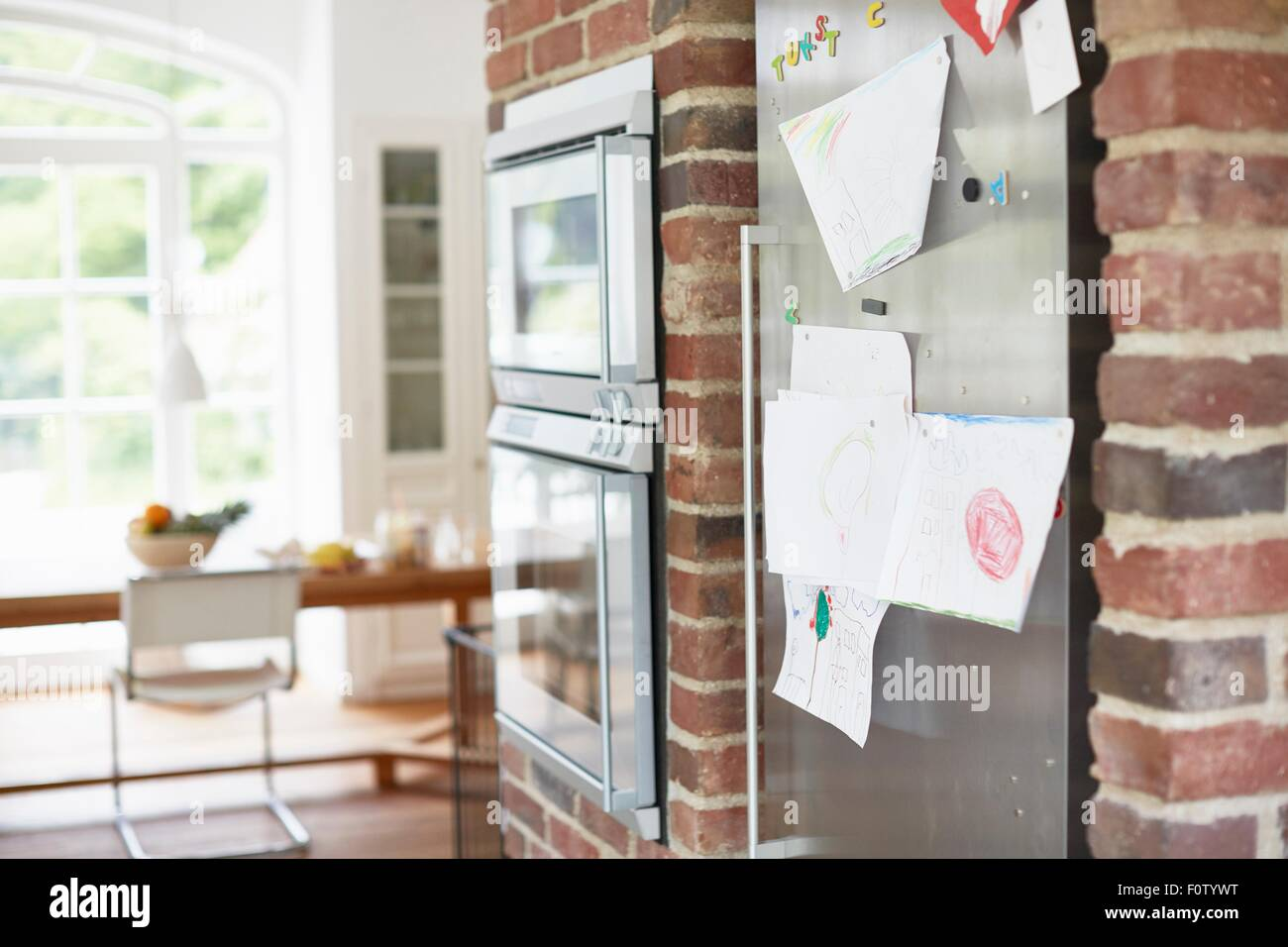 Children's drawings stuck on fridge door - Stock Image