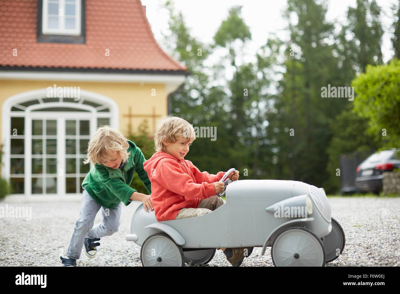 Two boys playing with vintage toy car in front of house - Stock Image