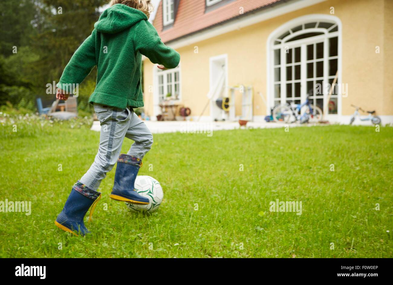 Rear view of boy wearing wellingtons playing football in the garden Stock Photo