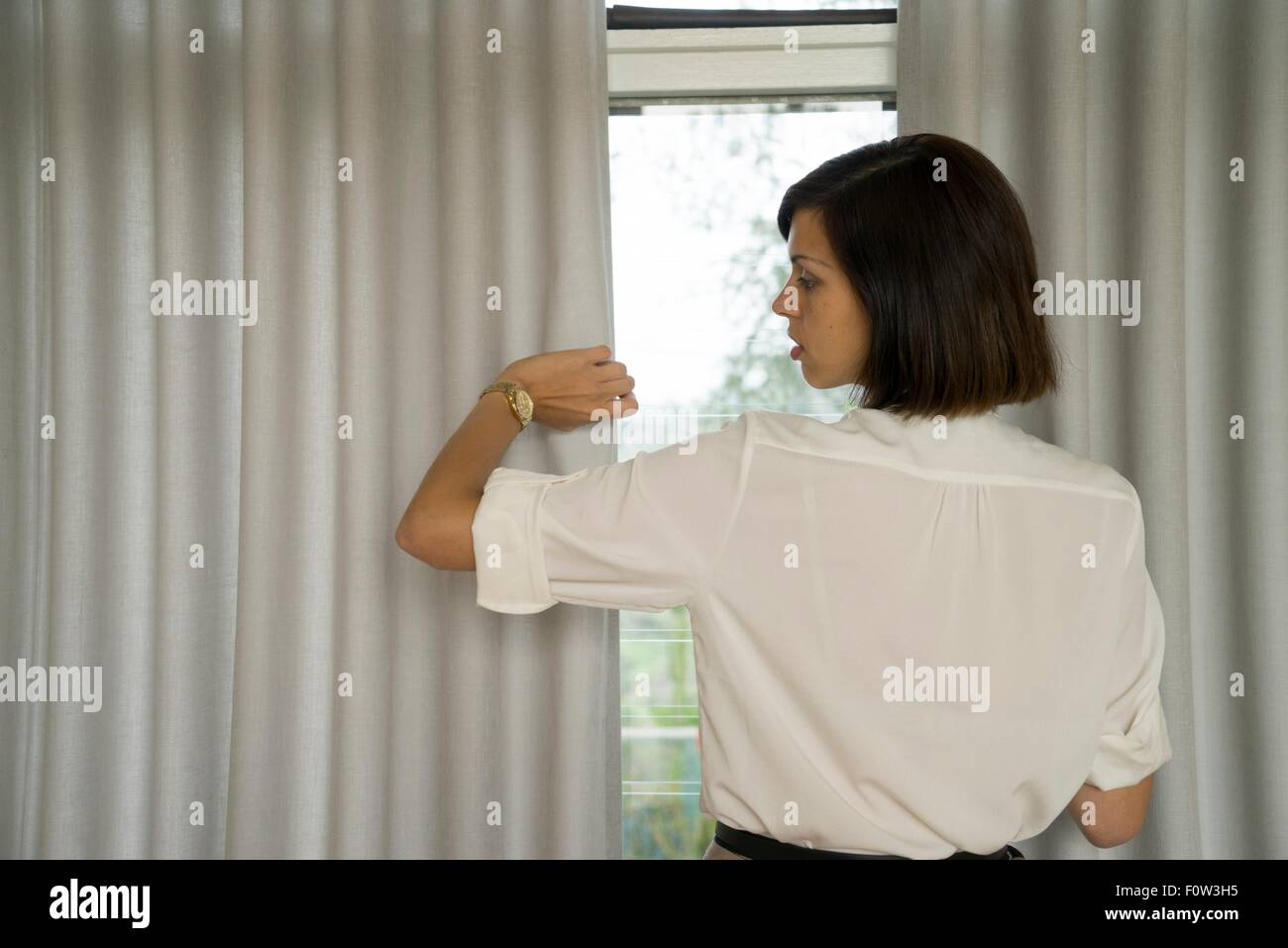 Businesswoman looking at wristwatch in front of window - Stock Image