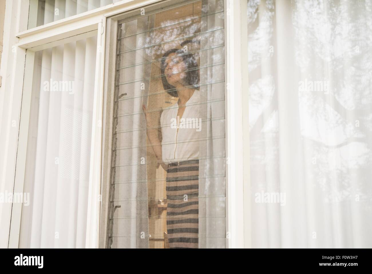 Mid adult woman looking out of house window - Stock Image